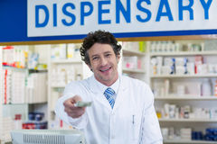 Pharmacist giving money to customer in pharmacy. Portrait of pharmacist giving money to customer in pharmacy Royalty Free Stock Images
