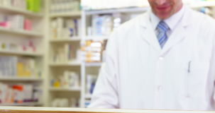 Pharmacist giving pill bottle to customer stock footage