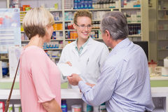 Pharmacist giving prescription to costumer Royalty Free Stock Photo