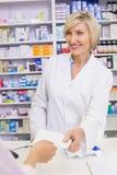 Pharmacist giving prescription to costumer Stock Images