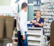 Pharmacist Giving Product To Customer In Pharmacy Royalty Free Stock Images