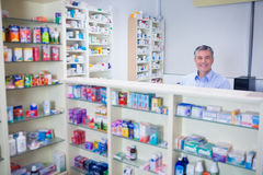 Pharmacist with grey hair standing behind shelves of drugs. In the pharmacy Royalty Free Stock Images