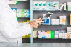 Pharmacist. Handsome Pharmacist with Digital Tablet in a Drugstore Royalty Free Stock Photos