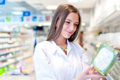 Pharmacist and health care worker in phamarcy. With medicine and drugs Royalty Free Stock Photography