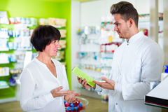 Pharmacist helping customers. Cheerful men pharmacist wearing white coat helping customers in pharmacy Royalty Free Stock Images