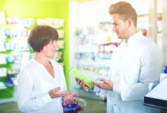 Pharmacist helping customers Royalty Free Stock Photography