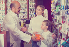 Pharmacist helping customers. Senior pharmacist standing with a cash desk in the pharmacy and helping customers Stock Photo