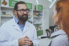 Pharmacist helping his female customer at drugstore royalty free stock photo