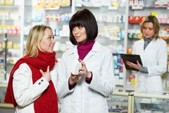 Pharmacist helps to drug purchaser Stock Photography