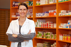 Pharmacist with her arms crossed. Happy pharmacist with her arms crossed in a drugstore Stock Image