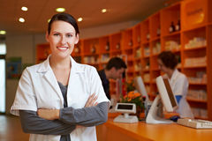 Pharmacist with her arms crossed. Happy pharmacist with her arms crossed in a pharmacy Royalty Free Stock Images