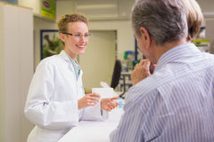 Pharmacist and her customers talking about medication Royalty Free Stock Images