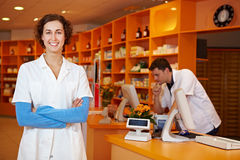 Pharmacist in her pharmacy. Happy pharmacist with arms crossed in her pharmacy Stock Photos