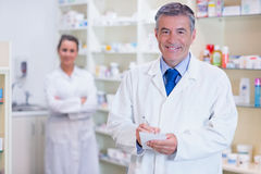 Pharmacist and his trainee with arms crossed behind Royalty Free Stock Photos