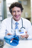 Pharmacist holding blood pressure monitor in pharmacy Royalty Free Stock Photos