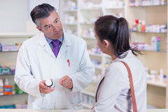 Pharmacist holding a bottle of drugs talking to customer Stock Photo