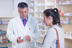 Pharmacist holding a bottle of drugs talking to customer Stock Images