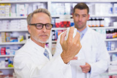 Pharmacist holding a box of pills while reading the label Royalty Free Stock Image