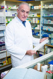 Pharmacist holding a clipboard in pharmacy Stock Photos