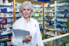 Pharmacist holding a clipboard in pharmacy. Portrait of pharmacist holding a clipboard in pharmacy stock images