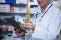 Pharmacist holding digital tablet while checking medicine. In pharmacy stock photo