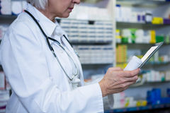 Pharmacist holding digital tablet while checking medicine. In pharmacy stock photos