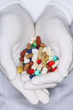 Pharmacist Holding Handful Of Pills. Closeup of pharmacist holding handful of pills Royalty Free Stock Images