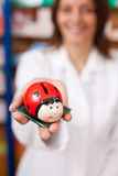 Pharmacist Holding Ladybird Shaped Coinbank Stock Photos