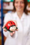 Pharmacist Holding Ladybird Shaped Coinbank. Female pharmacist holding ladybird shaped coinbank at pharmacy Stock Photos
