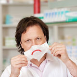 Pharmacist Holding Mask With Sad Smiley Royalty Free Stock Photos