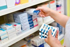 Pharmacist holding medicine box and capsule pack. In pharmacy drugstore royalty free stock image