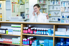 Pharmacist holding medicine box while talking on phone. In pharmacy Stock Photography