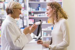 Pharmacist holding medicine box talking to customer Royalty Free Stock Photography