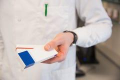 Pharmacist holding medicine boxes Stock Image