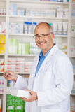 Pharmacist Holding Medicine And Prescription Paper In Pharmacy Royalty Free Stock Images