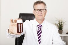 Pharmacist holding out a bottle of pills. Middle aged male pharmacist or doctor holding out an unlabeled brown plastic bottle of pills as he sits at a desk in an Royalty Free Stock Photography