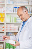 Pharmacist holding package and prescription Stock Images
