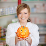 Pharmacist holding piggy bank Stock Images