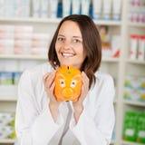 Pharmacist Holding Piggybank In Pharmacy Stock Photography