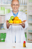 Pharmacist Holding Plate Of Fruits At Pharmacy Royalty Free Stock Images