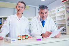 Pharmacist holding a prescription next to his trainee Royalty Free Stock Image