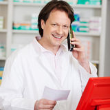 Pharmacist Holding Prescription Paper While On Call Royalty Free Stock Photo