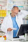 Pharmacist Holding Prescription Paper At Counter Stock Image