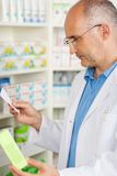 Pharmacist Holding Prescription Paper And Medicine Royalty Free Stock Photo