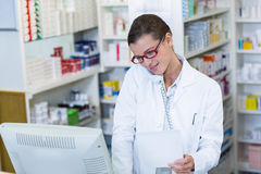 Pharmacist holding prescription paper while talking on phone Stock Photos