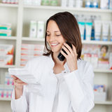Pharmacist Holding Prescription Paper While Using Cordless Phone. Mid adult female pharmacist holding prescription paper while using cordless phone in pharmacy stock images