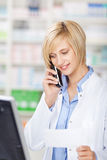 Pharmacist Holding Prescription Paper While Using Cordless Phone. Young female pharmacist holding prescription paper while using cordless phone in pharmacy royalty free stock photo