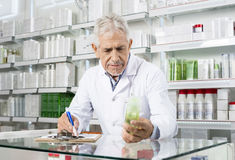 Pharmacist Holding Product While Writing On Clipboard. Senior pharmacist holding product while writing on clipboard in pharmacy royalty free stock photos