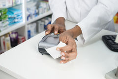 Pharmacist Holding Receipt While Pressing Card Reader`s Button Stock Photo