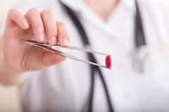 Pharmacist holding tweezers with pill Royalty Free Stock Image